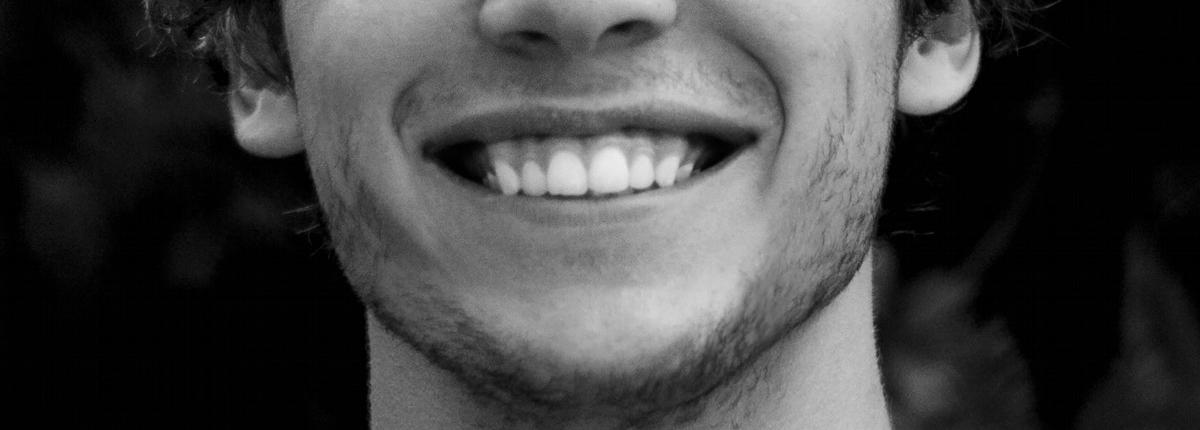k&k zahnaerzte mobilodent junger Mann zeigt schöne Zähne beim Lächeln