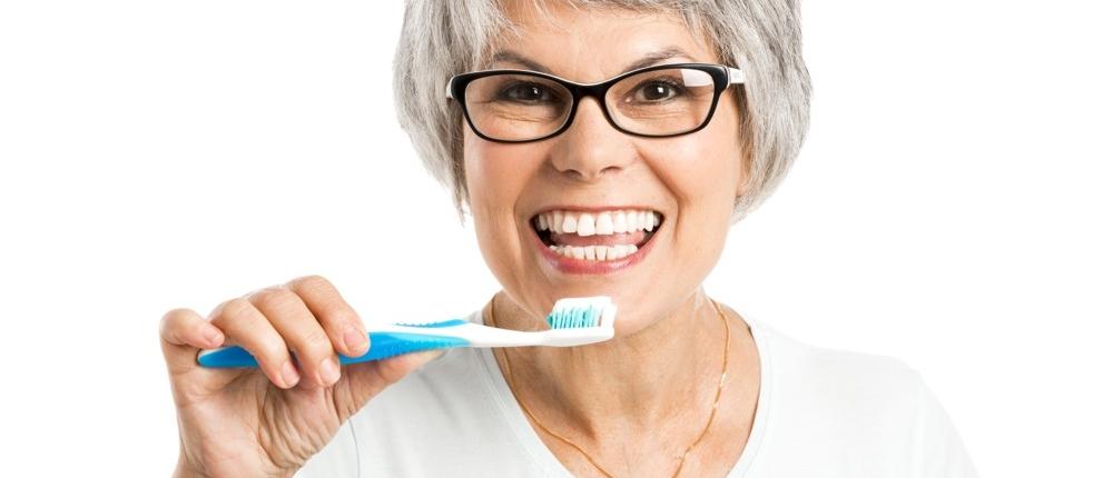 k&k zahnaerzte mobilodent lächelnde Frau beim Zähneputzen